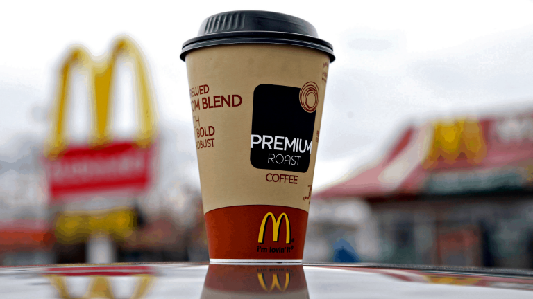 McDonalds Decaf Iced Coffee on hood of a car in the McDonalds parking lot.